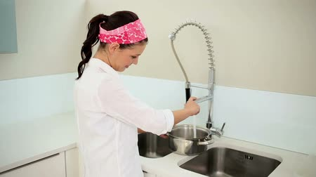 раковина : Beautiful brunette filling a pot with water in the kitchen at home Стоковые видеозаписи