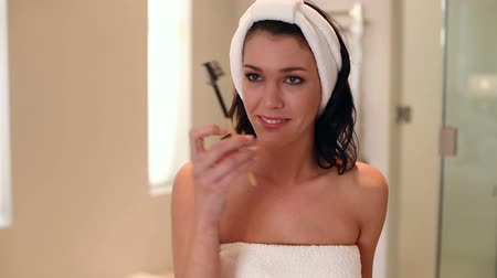 towel : Beautiful brunette wearing a towel doing her eyebrows at home in the bathroom
