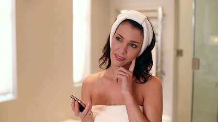 banyo : Beautiful brunette wearing a towel sending a text at home in the bathroom