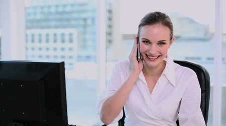 profi : Smiling businesswoman having a phone call in her office Stock mozgókép