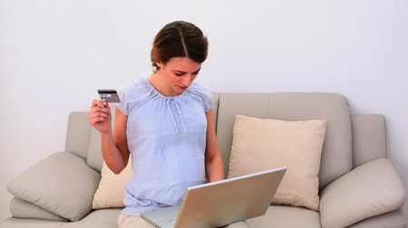 dörzsölés : Pregnant woman using her laptop for shopping online on the sofa at home in the living room