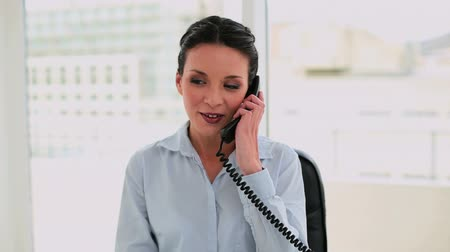 брюнет : Happy businesswoman answering the phone in her office