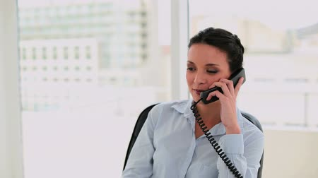 брюнет : Happy businesswoman talking on the phone in her office