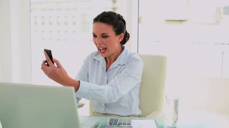 amarrado : Angry businesswoman hanging up the phone in her office