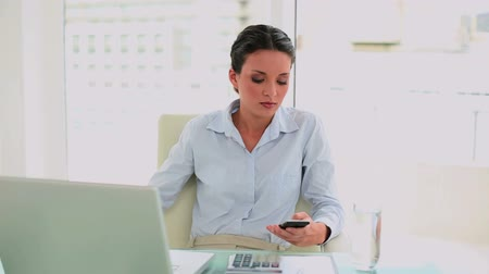 amarrado : Pretty businesswoman texting on her smartphone in her office Vídeos