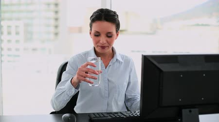 amarrado : Businesswoman drinking water at her desk in her office