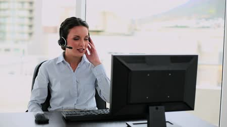 amarrado : Call center agent on a call at her desk in her office Vídeos