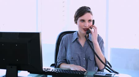 диалог : Pretty businesswoman answering phone at her desk in office Стоковые видеозаписи