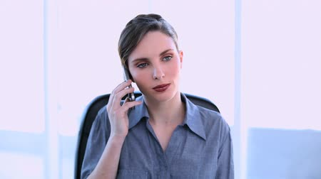 брюнет : Happy businesswoman answering smartphone at her desk in office