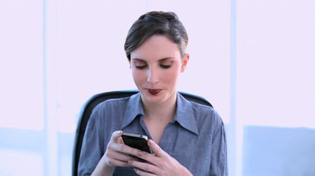 amarrado : Happy businesswoman texting on her smartphone at her desk in office