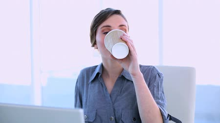 amarrado : Happy businesswoman working on a laptop having a coffee at her desk in office