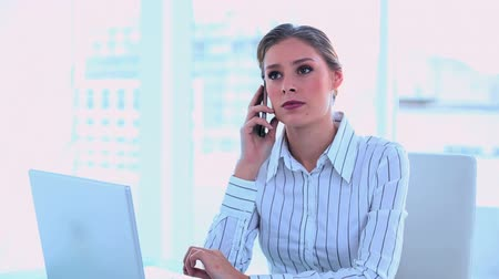 mluvení : Thoughtful brunette businesswoman making a phone call at office
