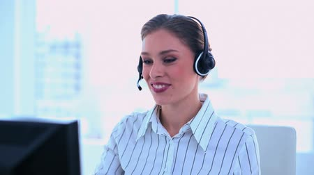 amarrado : Smiling attractive brunette operator making a phone call at office Vídeos