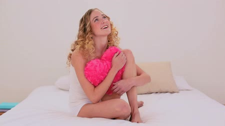 объятие : Thoughtful blonde model cuddling a heart shaped pillow sitting on her bed