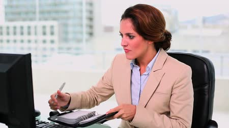 amarrado : Concentrated attractive businesswoman filling her diary at office Vídeos