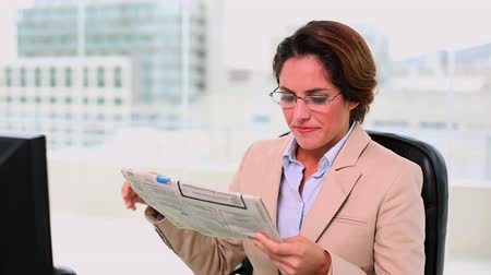 amarrado : Concentrated attractive businesswoman reading a newspaper at office