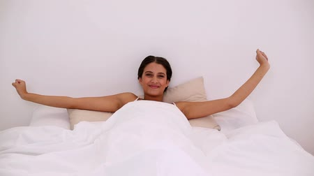 yatak kıyafeti : Pleased attractive woman waking up peacefully in her bed