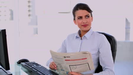 amarrado : Thoughtful beautiful businesswoman using computer while reading newspaper at office