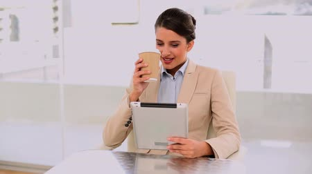 amarrado : Smiling beautiful businesswoman using a laptop while drinking coffee at office