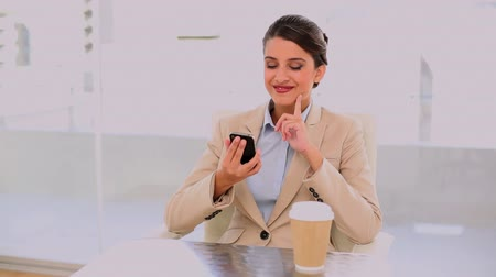 amarrado : Happy beautiful businesswoman drinking coffee while using mobile phone at office