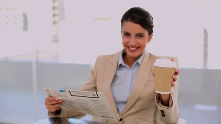 amarrado : Relaxed beautiful businesswoman drinking coffee while reading newspaper at office