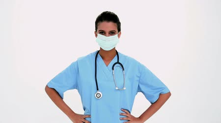 giyme : Smiling beautiful nurse putting a surgical mask on white background