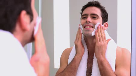 barbear : Handsome man applying shaving foam in bathroom