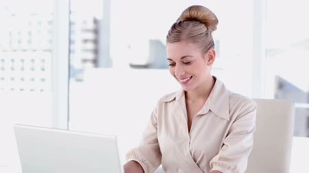 amarrado : Smiling blonde businesswoman using laptop in bright office Vídeos