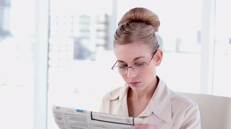 amarrado : Content blonde businesswoman reading newspaper in bright office