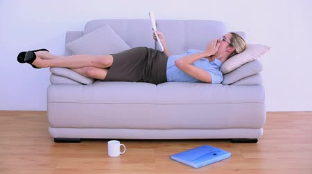 bizneswoman : Stylish tired businesswoman falling asleep on couch in bright living room Wideo