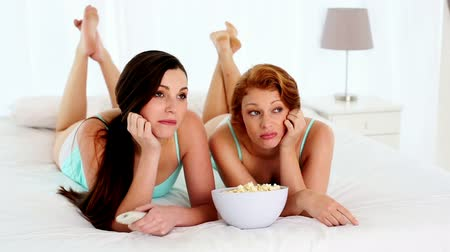 fekvő : Attractive bored women watching television lying on bed in bright bedroom Stock mozgókép