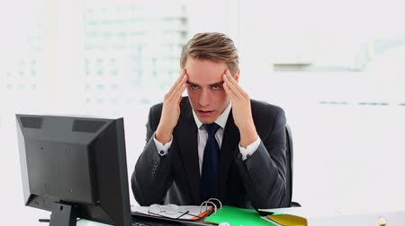 bosszús : Attractive businessman suffering from headache sitting at his desk