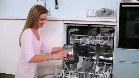 placas : Beautiful calm woman filling the dish washer in the kitchen