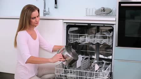 ajoelhado : Annoyed woman filling the dish washer in the kitchen Vídeos