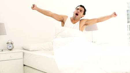 peaceful : Tired handsome man yawning in bright bedroom