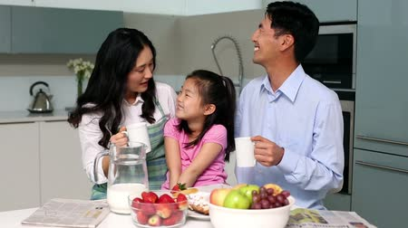 kahvaltı : Happy family sitting at breakfast table in bright kitchen