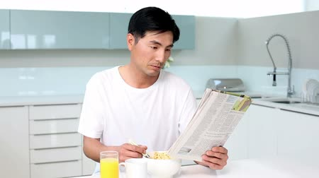 časopis : Attractive man eating cereal and reading magazine in bright kitchen
