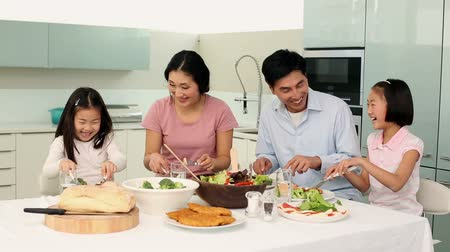 Happy family having dinner together at home in the kitchen Vídeos