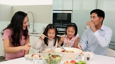 vacsora : Happy family having spaghetti dinner together at home in the kitchen Stock mozgókép