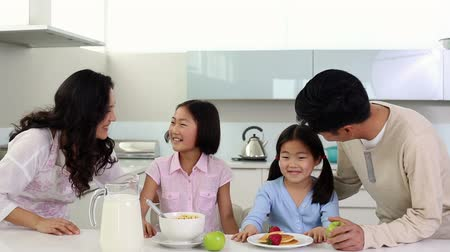 kahvaltı : Parents serving breakfast to their cute daughters at home in the kitchen