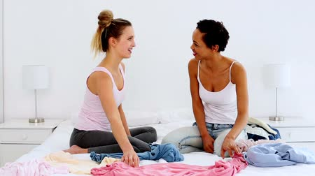 pizsama : Two pretty friends jokingly fighting over clothes on bed at home in bedroom Stock mozgókép