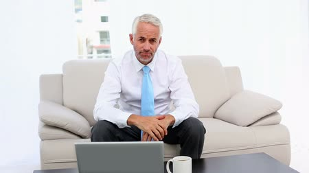 ideges : Stressed businessman looking at laptop then camera in office staff room Stock mozgókép