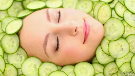 posando : Natural womans face surrounded by cucumber slices smiling at camera