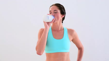 брюнет : Fit brunette drinking from sports bottle and smiling at home