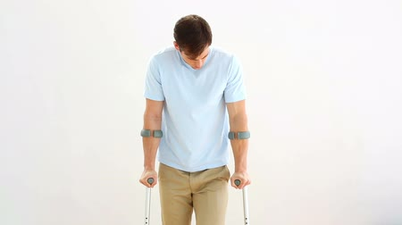 kule : Injured man on crutches stepping towards camera on white background