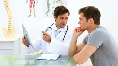 fizjoterapeuta : Handsome doctor discussing xray with his patient in his office at the hospital