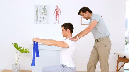 terapeuta : Physiotherapist checking shoulders of patient pulling resistance band in his office at the hospital