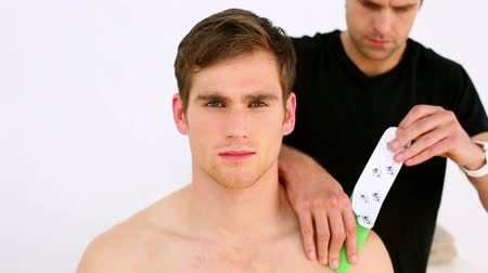 fizjoterapeuta : Physiotherapist applying kinesio tape to patients shoulder in his office at the hospital