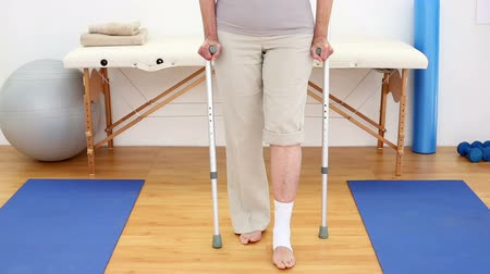 kule : Injured patient in crutches walking towards camera in an office at the hospital Wideo