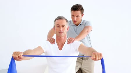 terapeuta : Physiotherapist checking patient stretching blue resistance band at the rehabilitation center